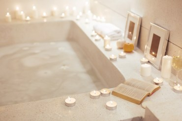 Luxury bathroom with jacuzzi bath surrounded by candles