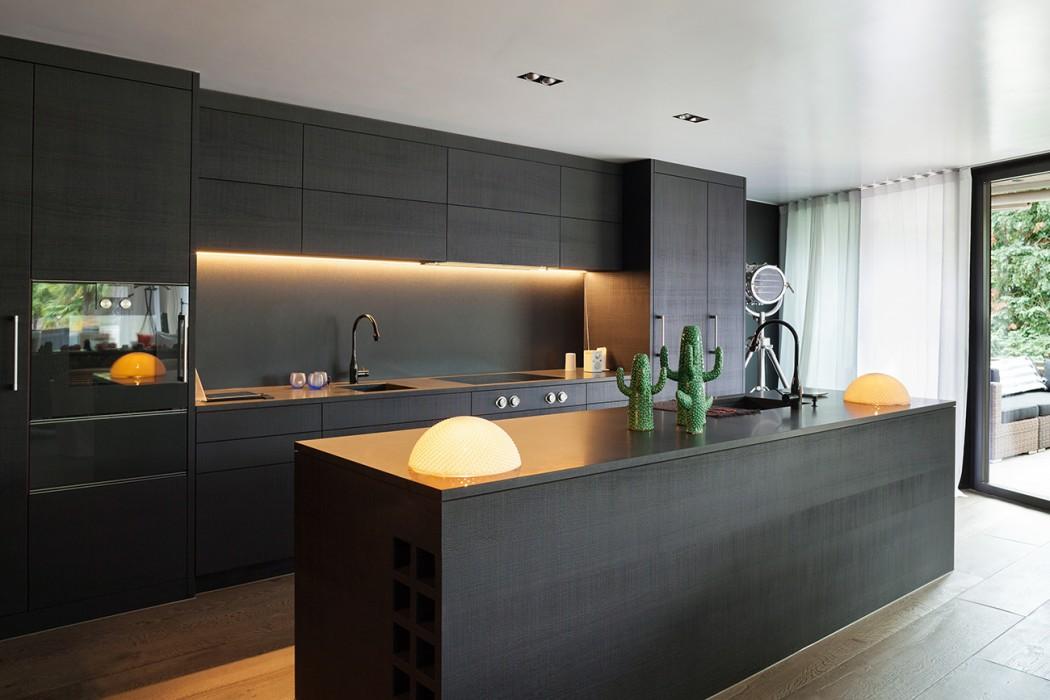 Modern minimalist kitchen with black kitchen cupboards, under cupboard warm lighting and wooden flooring