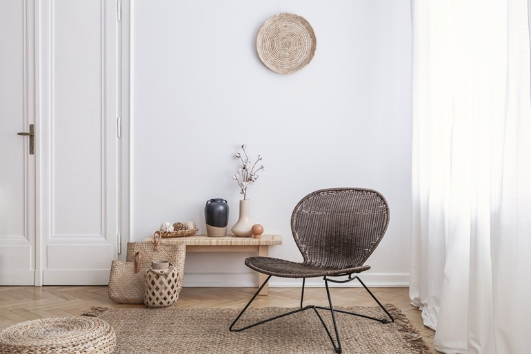 Relaxing interiors with natural woven material rug, pouf, chair, hats and bags