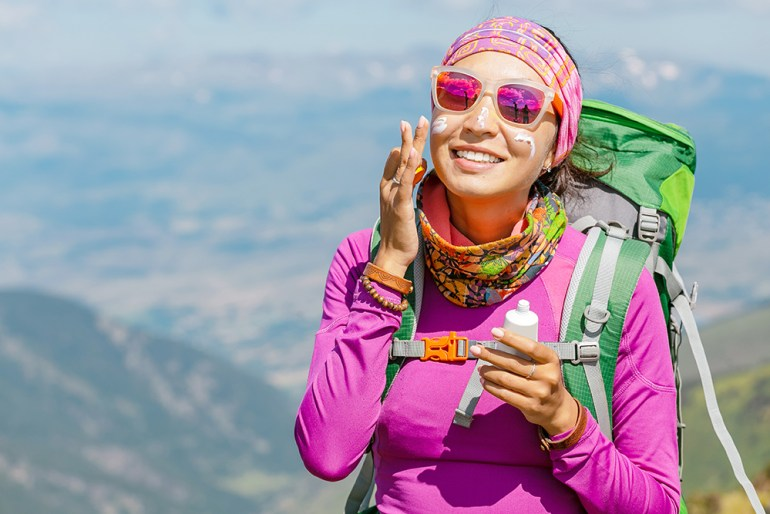 Women hiking with backpack on. Whereing sunglass and suncream
