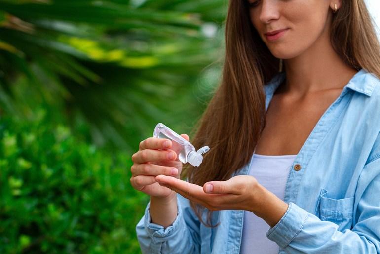 Women stood next to large plants, using hand sanitiser