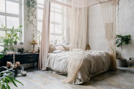 Boho chic bedroom with king size four poster bed. Bohemian bedroom with dark furniture and plants