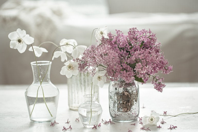 Bud vases with small white flowers and a bunch of pink flowers