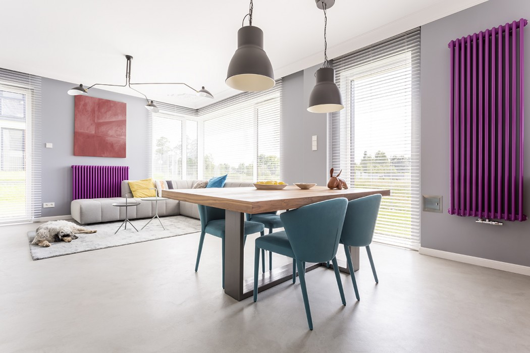 Modern living room with blue dining table chairs and purple radiator