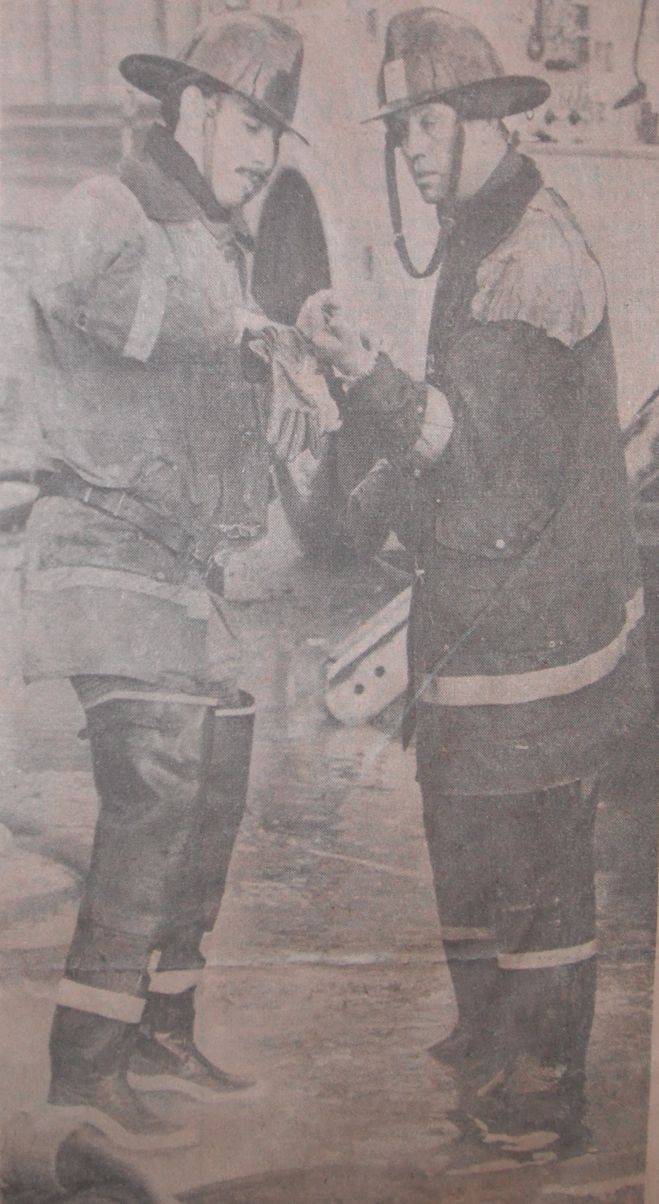 London Firemen Morley Hanes, left, and Don Varey stop for a moment to attend to an injury to Mr. Varey's hand. (photo by Rick Eglington of The London Free Press)