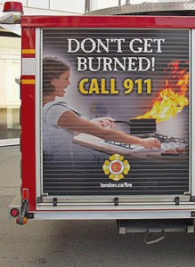 A billboard on a London fire truck that depicts a woman moving a pot, that has caught on fire, off the stove reads 'Don't get burned! Call 9-1-1.'
