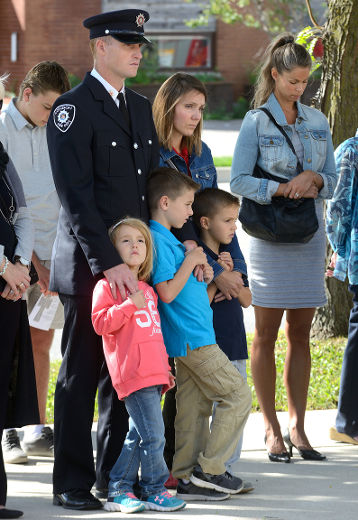 London Firefighter Dennis Peeters observes a moment of silence with his wife Melisa and children Lauren, 4, Luka, 7, and Julian, 6, l-r, during a ceremony to remember firefighters who died in the line of duty at London Fire Station No.1 on Sunday September 11, 2016. The ceremony is held annually on September 11 to remember the firefighters who died in the World Trade Tower attacks on September 11, 2001. (MORRIS LAMONT/THE LONDON FREE PRESS /POSTMEDIA NETWORK)