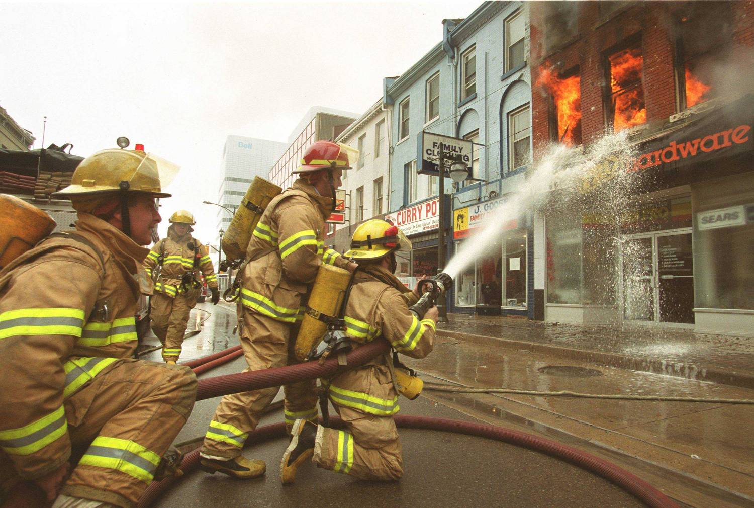Firefighters using large hoses to extinguish second floor fire fire in a downtown hardware store.