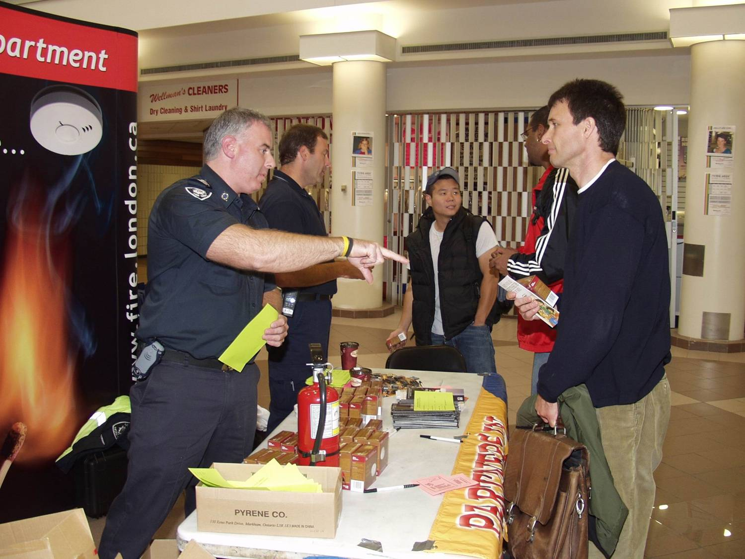 Fire Prevention officer explaining fire safety to citizens at a public display.