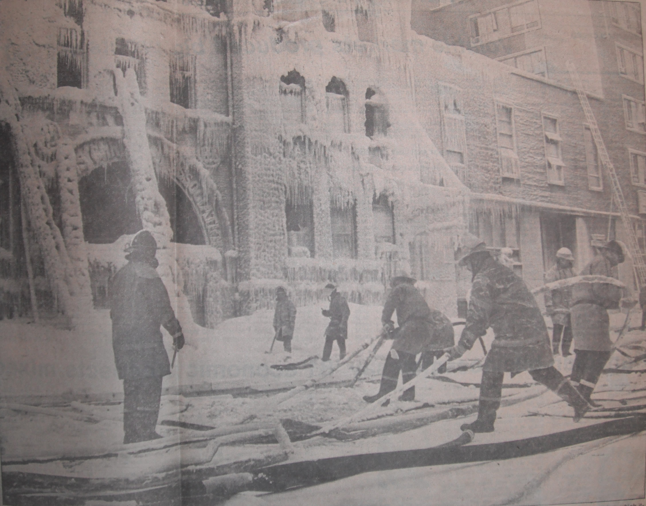 Firefighters pulling frozen lines from the ice that formed during the fire at the YM-YWCA fire.