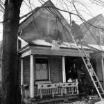Fire fighters working from a ladder and on the front porch of a home with light smoke showing