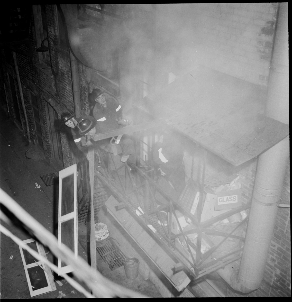 Four fire fighters battling smoke on a second floor fire escape