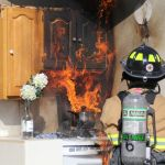 Fire fighter standing in front of stove that is on fire