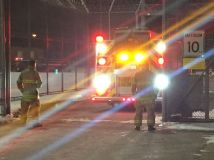 Fire fighters backing up firetruck with lights flashing in front of jail