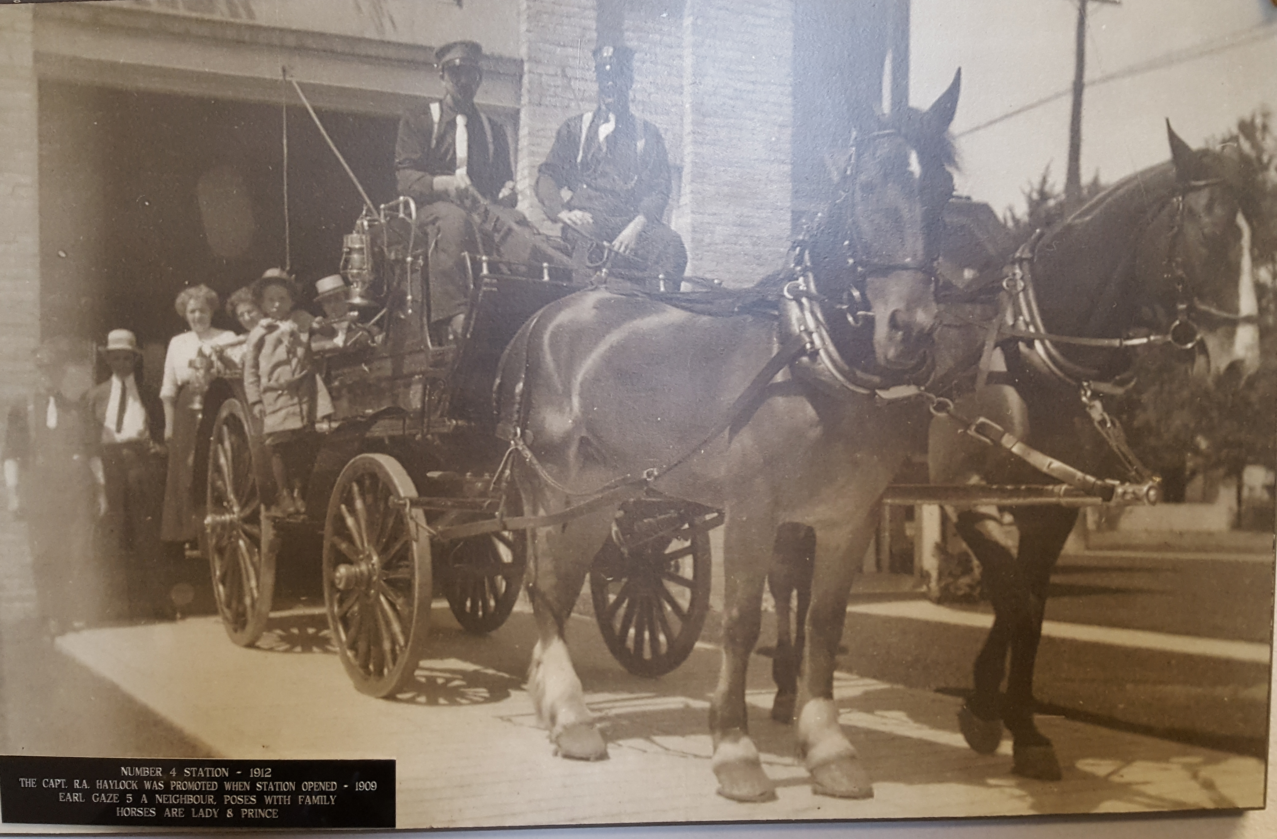 Crew pose with horses and apparatus in front of station with neighours.