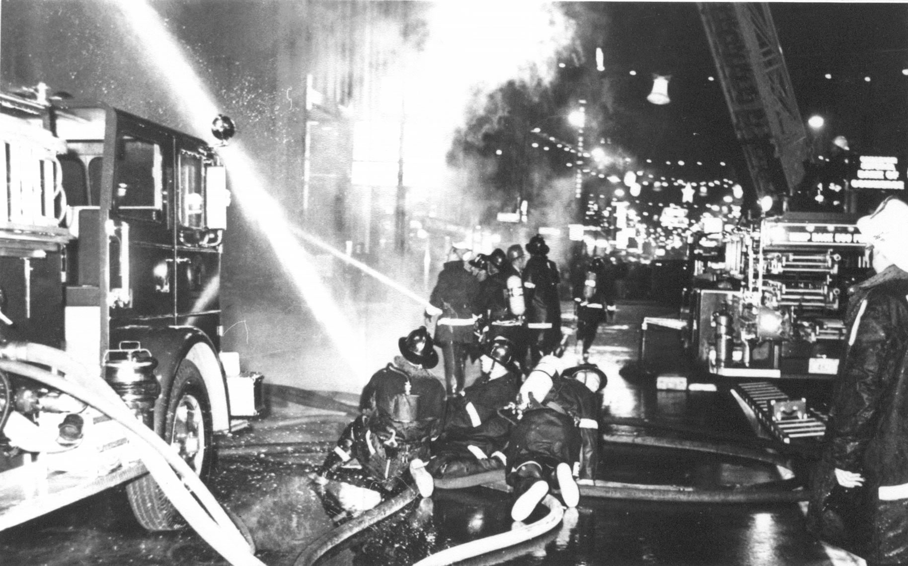 Firefighters manning large hose streams to extinguish a four story fire.