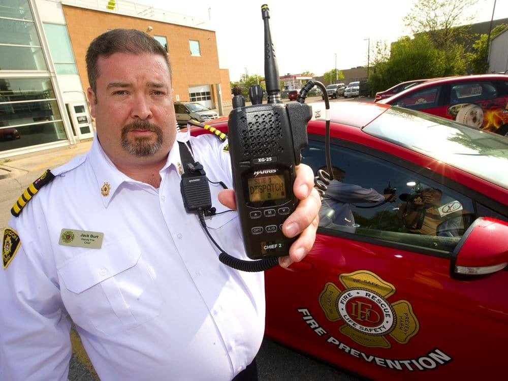 Assistant Deputy Chief holds a portable radio