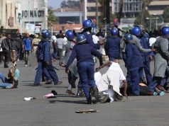 Riot police class with protesters in Zimbabwe