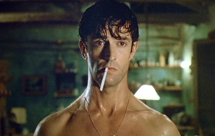Rupert Everett looking brooding with a cigarette in Cemetery Man