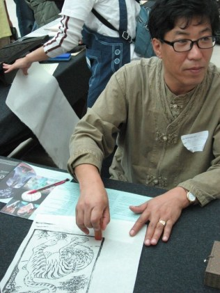 Ahn Jun-young affixing his chop to one of his woodcuts