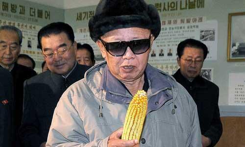 Kim Jong Il looking at a corn cob