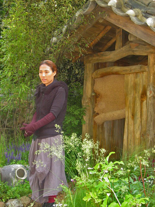 Jihae Hwang in front of the outside toilet, the centrepiece of her garden design