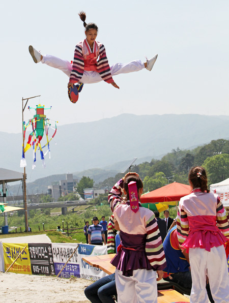 "A girl jumps while playing ""neolttwigi,"" a traditional Korean game on a seesaw-like plank, at the Gangneung Dano Festival in Gangneung, Gangwon-do"