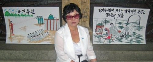 Kim Hye Sook with two of her paintings