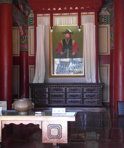 A small shrine to Yi Sun-shin in his command centre. The blue roof of the entrance gate is reflected in the glazing of the memorial portrait