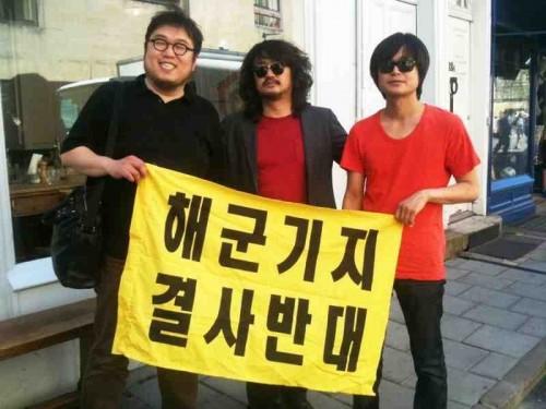 Three-quarters of the Naneun Ggomsuda team display their banner opposing the Jeju naval base