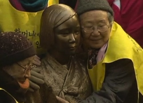 Two real life Comfort Women embrace embrace the statue of their younger selves opposite the Japanese Embassy in Seoul