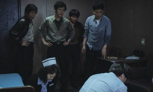 An early scene: medics try to resuscitate the dead student, as the police interrogators look on.