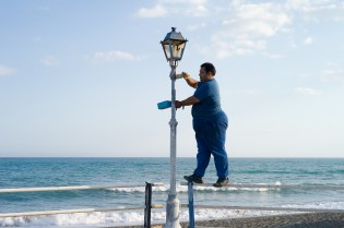 A ma is painting a lanterne at the shore of Crete