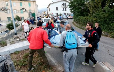 People stand along the road following a quake in Amatrice, central Italy, August 24, 2016. REUTERS/Remo Casilli