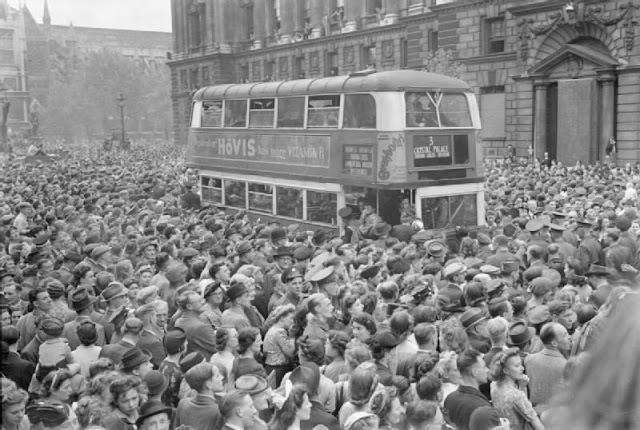 A number 3 double-decker bus slowly pushes its way through the huge crowds gathered in Whitehall to hear Churchill's Victory speech and celebrate Victory in Europe Day
