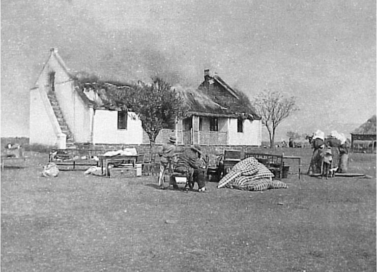 Boer family watch their home burning during the Anglo-Boer War (https://commons.wikimedia.org/wiki/File:VerskroeideAarde1.jpg)