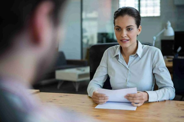 Business executive conducting job interview with man