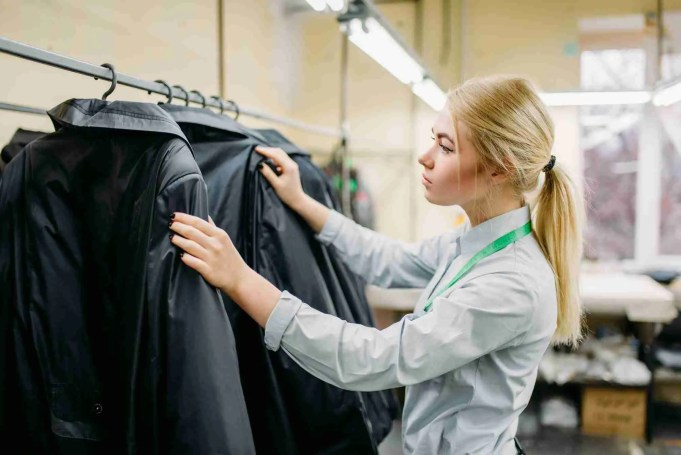 Clothes designer measures length sleeve jacket