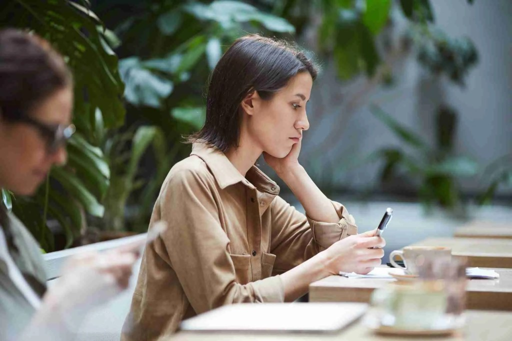 Puzzled woman examining article in cafe