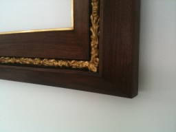 4'' wide double wedge profile with a running pattern at the height of the frame. Shown in walnut and 22 karat gold leaf