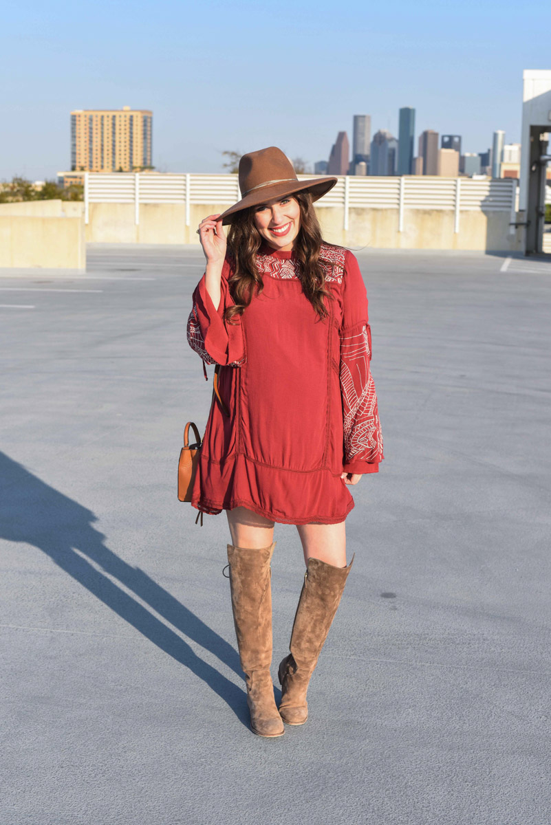 Houston fashion blogger Alice Kerley styles a Planet Blue bohemian red mini dress as a maternity dress with a pair of Elaine Turner suede over the knee boots.