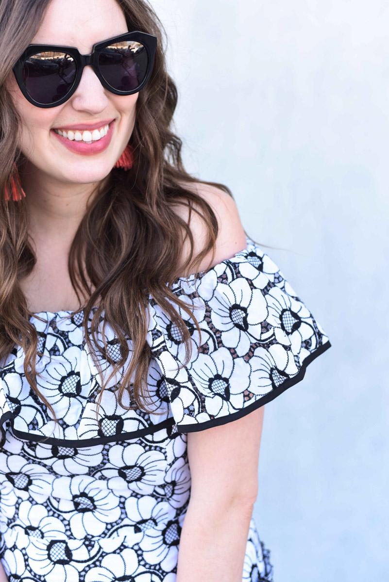 A floral off the shoulder dress with Karen Walker black sunglasses.