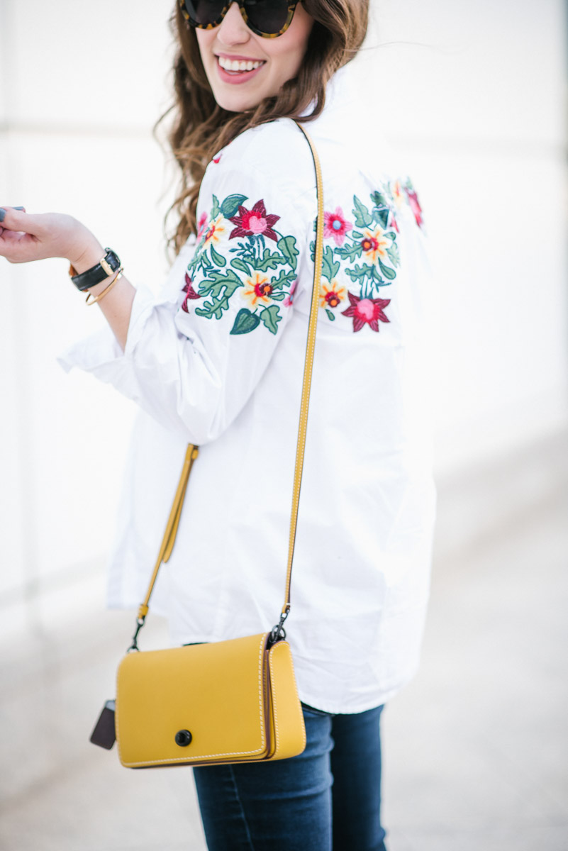 Embroidered White Button down styled with skinny jeans and the coach dinky bag in yellow.
