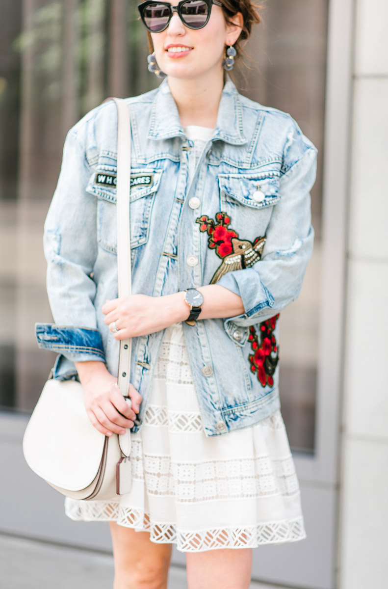 Embroidered denim jacket with a white coach saddlebag.