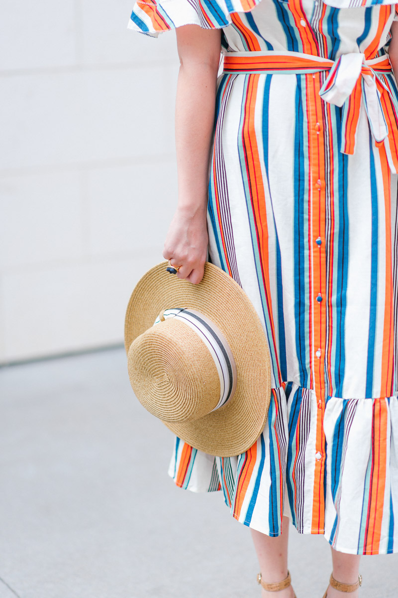 Houston blogger styles a striped moon river off the shoulder dress with a boater hat