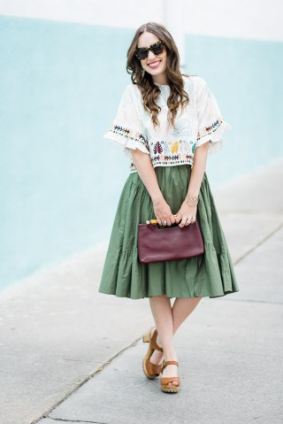 Houston fashion blogger styles a boho embroidered crop top with a green midi skirt.