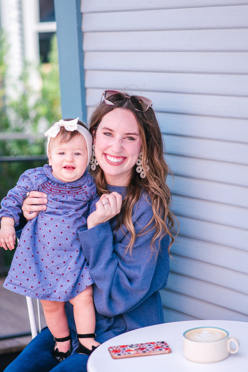Mother Daughter Duo in a Boden Mini Polka Dot Dress, A goodnight Macaron Blue Sweater, and Lisi Lerch ginger Earrings.