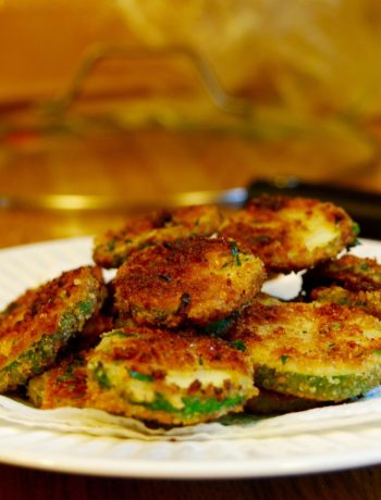 Pile of fried zucchini on a white plate.