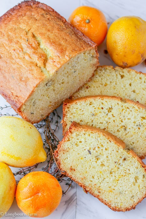 Three slices of citrus thyme bread next to a sliced loaf of bread with a lemon.