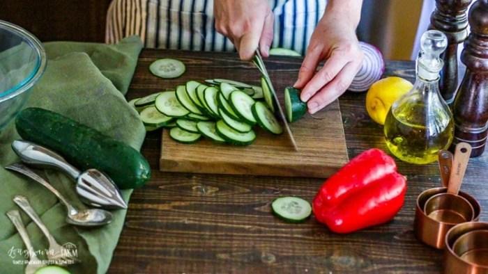 Slicing a cucumber on a cutting board.